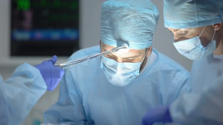 invasive : Assistant wiping main surgeon forehead during hospital operation, profession Stock Footage