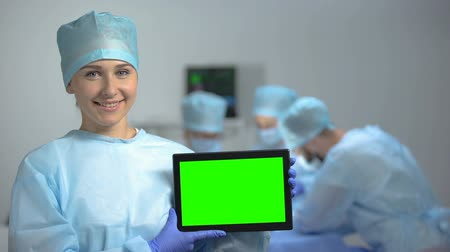 invasive : Smiling nurse holding tablet PC with green screen during operation, hospital ad
