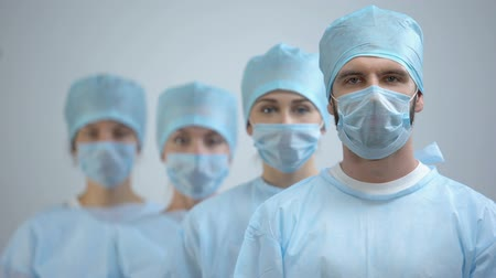 reanimation : Professional surgeon team in mask and uniform looking at camera, hospital work