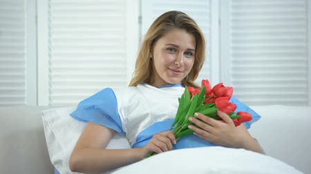 rendes : Smiling woman holding bunch of tulips in hospital, present after child birth