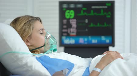 tlen : Stabilized woman in oxygen mask sleeping, intensive care hospital unit, surgery