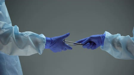matança : Surgeon giving scissors against dark background, illegal black-market surgery Stock Footage