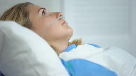 reanimation : Upset woman lying with oxygen nasal catheter on face, preparation for surgery