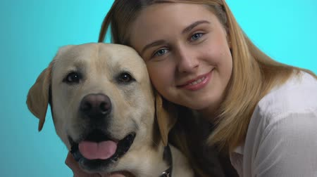 itaat : Pretty young woman and labrador dog looking camera closeup on blue background Stok Video