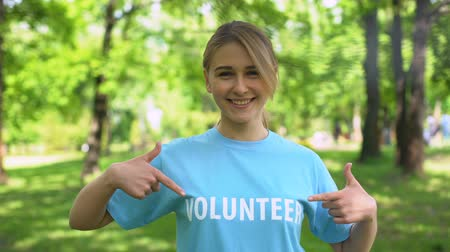 refah : Young pretty woman pointing at volunteer word on blue t-shirt, eco activist