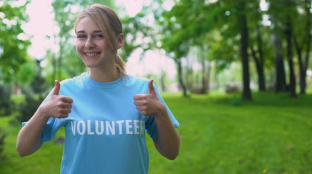 kciuk : Happy female volunteer showing thumbs up standing in forest, natural resources