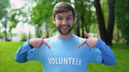 evento social : Happy male activist pointing at volunteer word on blue t-shirt, eco project Archivo de Video