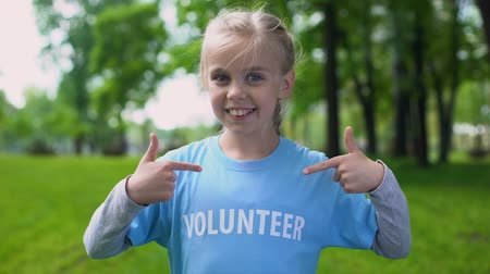 ekosistem : Happy schoolgirl pointing volunteer word on t-shirt, eco project participation Stok Video