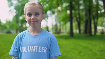 odpowiedzialność : Small female volunteer smiling on camera, environment protection, ecosystem