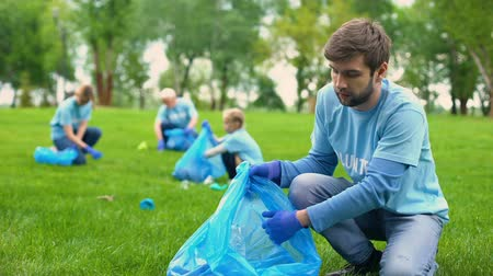 reciclagem : Happy male volunteer putting rubbish in garbage bag and smiling, responsibility