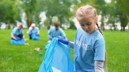 ekosistem : Responsible child volunteer collecting trash in garbage bag smiling on camera