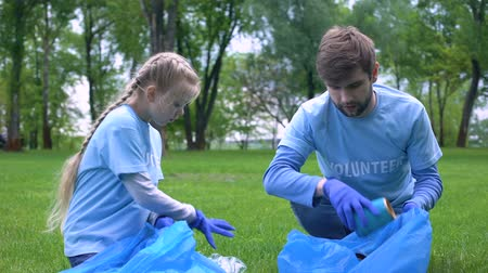 ekosistem : Male volunteer and daughter collecting garbage forest together, giving high five Stok Video