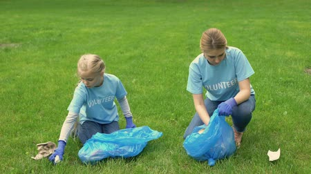 preservation : Young woman and schoolgirl giving high five collecting garbage in park, teamwork