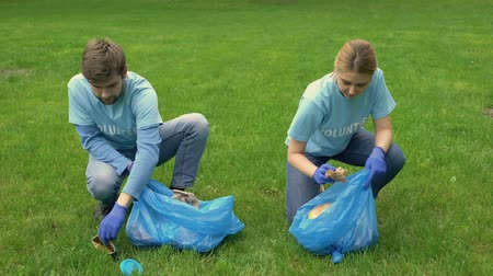 ekosistem : Male and female volunteers picking up litter in park smiling each other, ecology