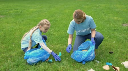 preservation : Schoolgirl and mother collecting rubbish in park, earth pollution, ecosystem