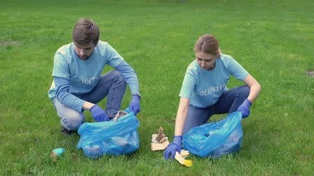 preservation : Young man and woman collecting garbage in bags giving high five, cleaning park