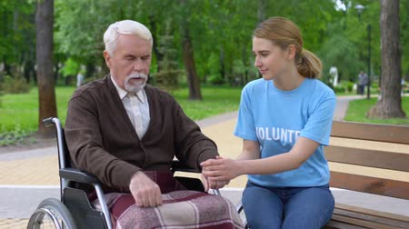 пенсионер : Pretty female volunteer supporting aged male patient in wheelchair, assistance