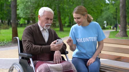 aiutante : Female volunteer helping disabled old man use smartphone, nursing home charity Filmati Stock