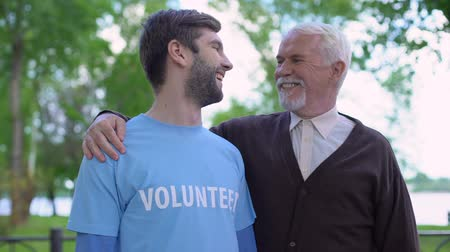 támogató : Young male volunteer and mature gentleman smiling to each other, social support