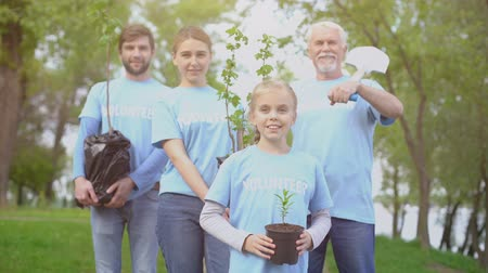 Łopata : Group of volunteers holding trees saplings and shovel, nature conservation