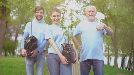ekosistem : Smiling eco activists holding tree saplings and shovel in hands, reforestation