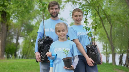volontariat : Parents and child in volunteer t-shirts holding potted trees nature conservation