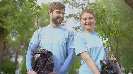obnovit : Young male and female volunteers smiling camera holding trees saplings, ecology