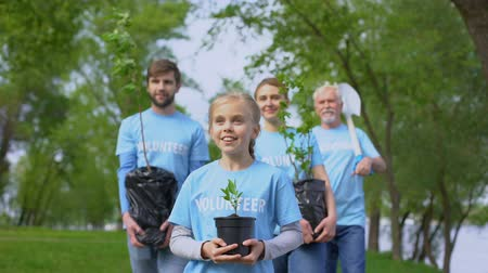 ekosistem : Eco volunteers walking park holding plant saplings shovel, nature conservation