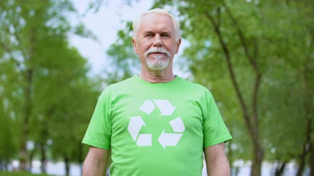 preservation : Senior man wearing recycling symbol t-shirt looking at camera, forest background Stock Footage