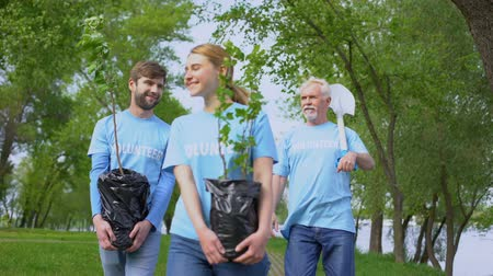 Łopata : Responsible eco activists walking park path holding green tree saplings shovel Wideo
