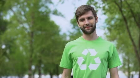 utilizzo : Handsome man in recycle symbol t-shirt looking camera, environmental protection