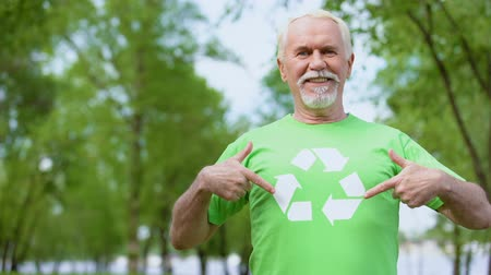activist : Smiling mature male pointing at recycling symbol on green t-shirt, ecology