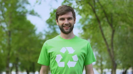 refah : Young eco activist in recycling symbol t-shirt smiling camera, wildlife care Stok Video