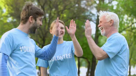odpowiedzialność : Smiling volunteers giving high five, cooperation gesture, environmental project