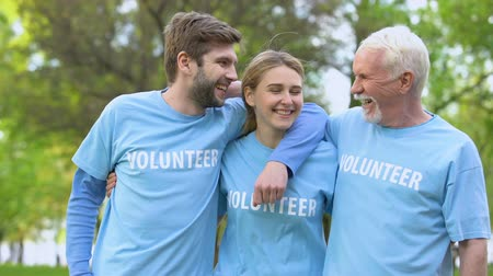 ekosistem : Three cheerful activists in volunteer t-shirts hugging, eco project achievement