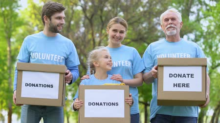 donate : Smiling volunteers holding donation boxes looking camera, charity project, help