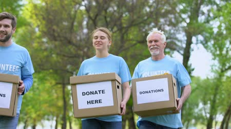 voluntário : Glad activists with donation boxes walking in park, charity foundation, help