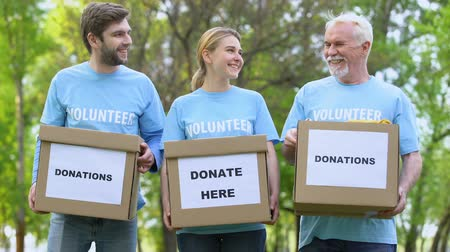 voluntário : Happy volunteers holding donation cardboxes, humanitarian aid assistance project