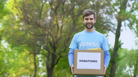 voluntário : Handsome male volunteer holding donation box with clothes standing outdoors