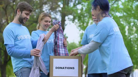 voluntário : Happy activists putting clothes donation box and giving high five, volunteering