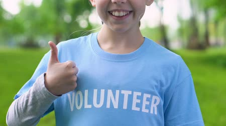 kciuk : Happy kid volunteer showing thumbs-up gesture in park, little eco-activist