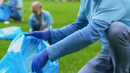 preservation : Volunteer team in gloves picking up litter in park, nature protection, ecology