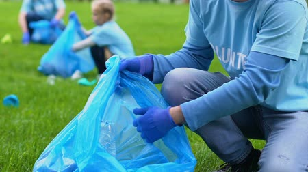 preservation : Smiling volunteer collecting rubbish in park, pollution problem, love to nature