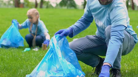 ekosistem : Group of volunteers picking litter in park, eco project participation, nature Stok Video