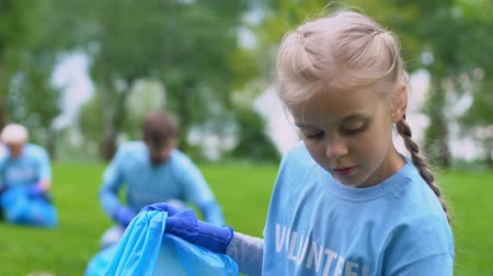 preservation : Little volunteer girl collecting rubbish in park, smiling on camera, nature care