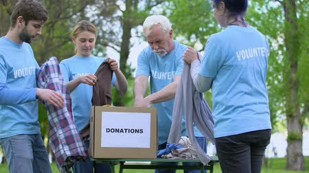voluntary : Volunteers sorting clothes putting in donation box, philanthropic organization