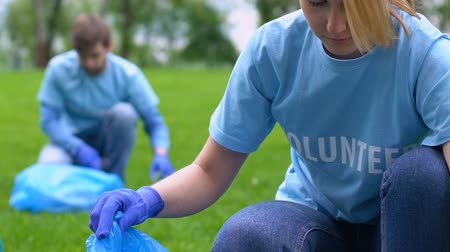 activist : Female eco-activist collecting rubbish in park, nature protection love to nature Stock Footage