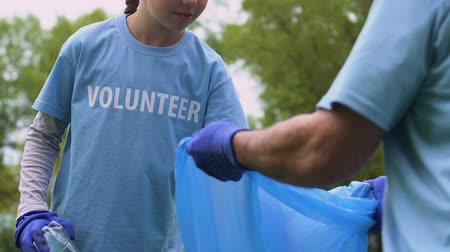 preservation : Female child putting trash into garbage bag, cleaning city park eco-volunteerism