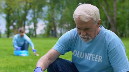 ekosistem : Elderly male volunteer collecting trash in park, smiling to camera, altruism