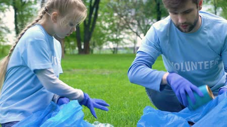 preservation : Kid and adult volunteers picking litter in park giving high-five, love to nature